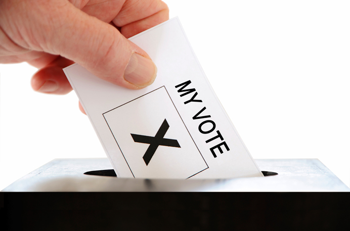 Hand putting a voting slip into a ballot box. You need to register for the Hobbayne by-election