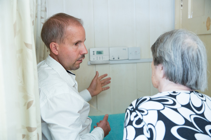 Mr Horgan's carer is shown how to use the new heating system by an advisor