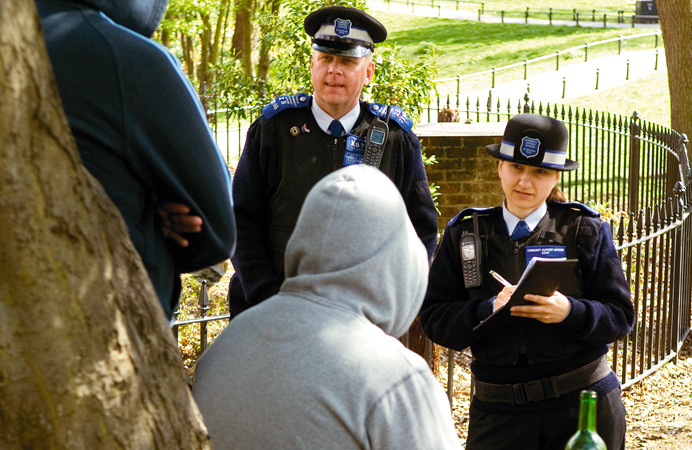 Officers talking to people with drink in a public park