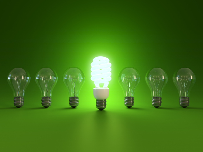 a energy saver lightbulb turned on in a line of switched off standard bulbs