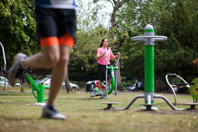 Using outdoor gym equipment in local park