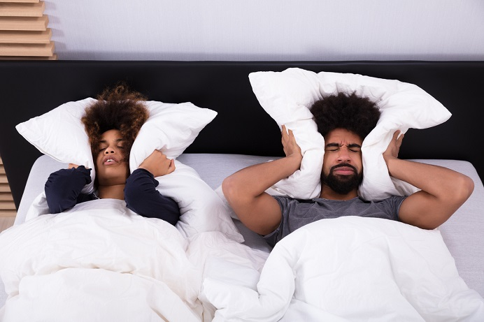 Couple laying in bed, covering their ears with their pillows