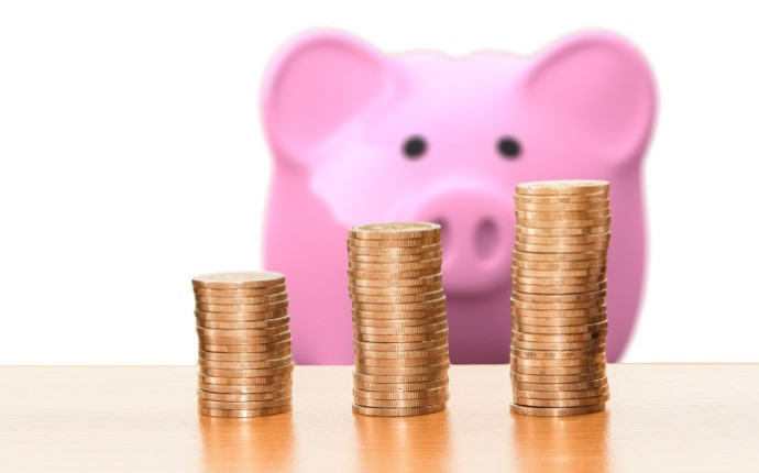 Pink piggy bank with stacks of coins in front