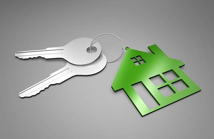 Set of silver keys on a green house shaped keyring
