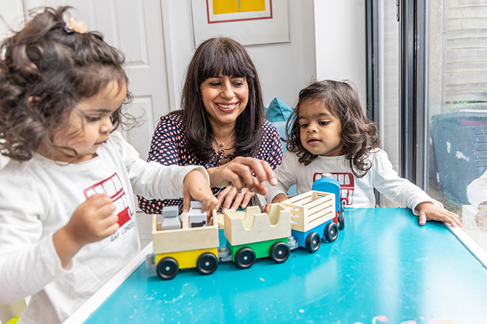 Simmi Bajaj, co-founder of Ealing Toy Library, playing with one of the toys with her daughters