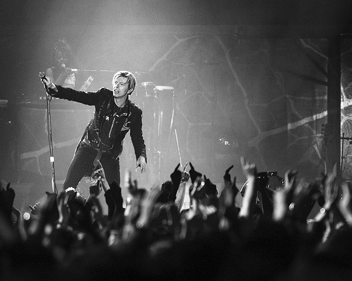 David Bowie performing - photo by Roger Woolman, via Wikimedia Commons