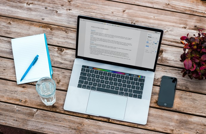 Laptop on a table with a glass of water, notebook and mobile phone
