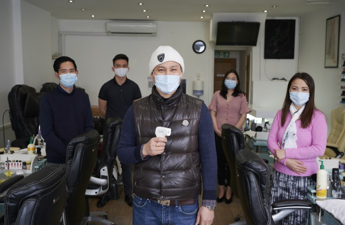 People with facemasks in nail bar