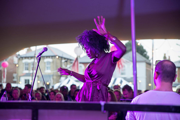 A singer dancing while performing at the Hanwell Hootie, with crowds behind looking on