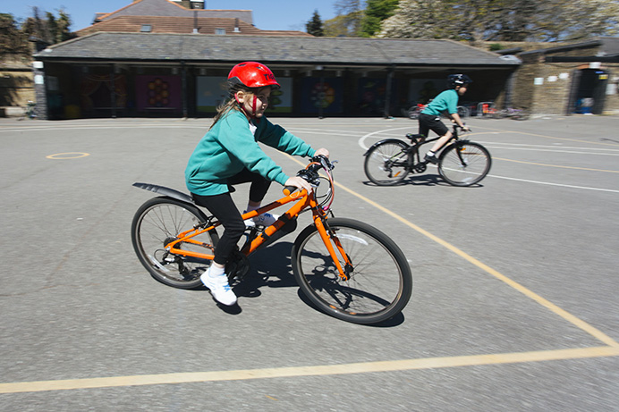 A girl school pupil riding a bike in a playground