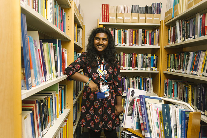 Project Choice student Kajani Ambikaiplan in the library, stacking shelves