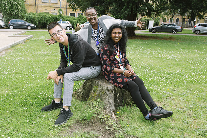 Sitting outside together on a tree stump: Project Choice: Student Aaron Parker, Annette Lafitte the project co-ordinator and student Kajani Ambikaiplan