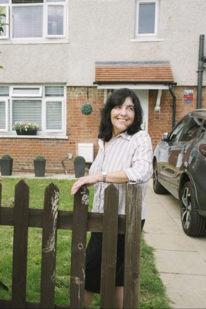 Woman standing at the end of a driveway in front of her house