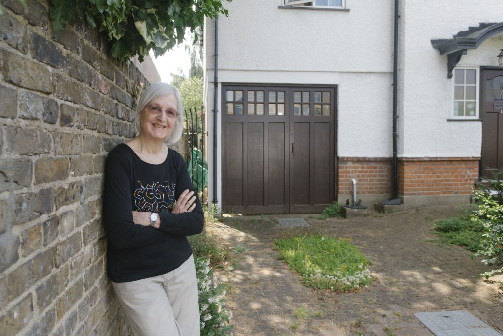 Woman standing in front of her driveway, which she has allowed to go 'green' with plants