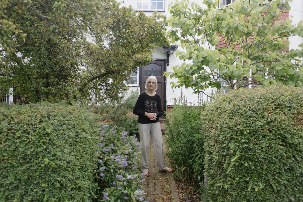Woman standing in green front garden, surrounded by bushes and plants