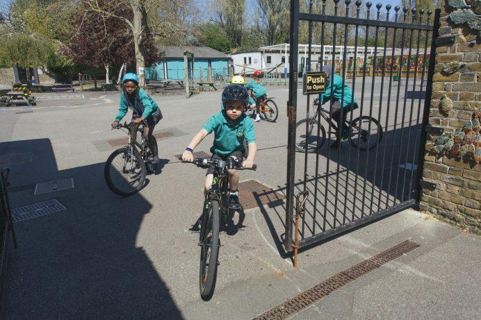 School pupils riding bikes through school gates
