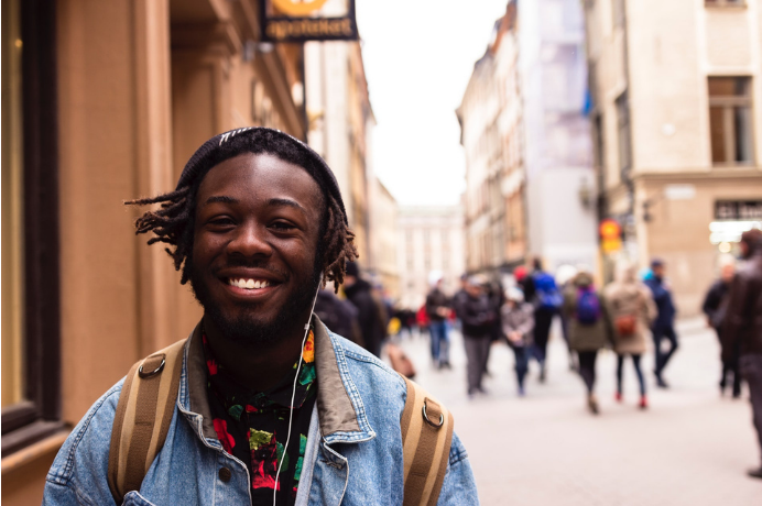 Young black man looking optimistic and happy in a high street