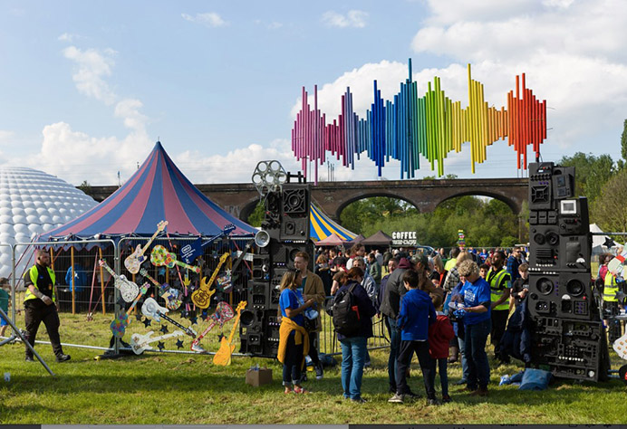 People entering the Hanwell Hootie music festival entrance. In the background is a colourful big top tent