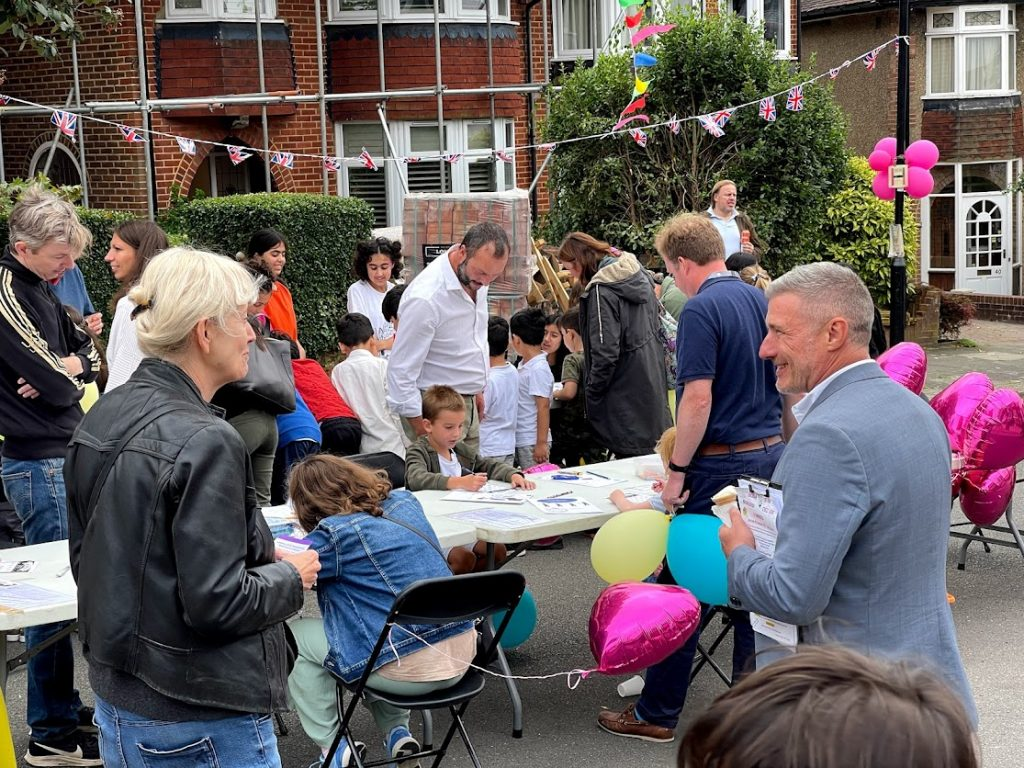 Adults watching children sitting at a table doing arts and crafts at a street party