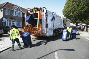Recycling truck and bin collectors in a street collecting recycling from bins