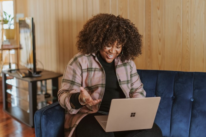 Lady looking happy using a laptop