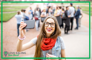 girl taking a selfie with blurred walking tour group in background