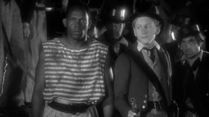 A man wearing an old striped sailor's uniform standing next to a ship's captain holding an old fashioned pistol - scene from 1935 movie Midshipman Easy
