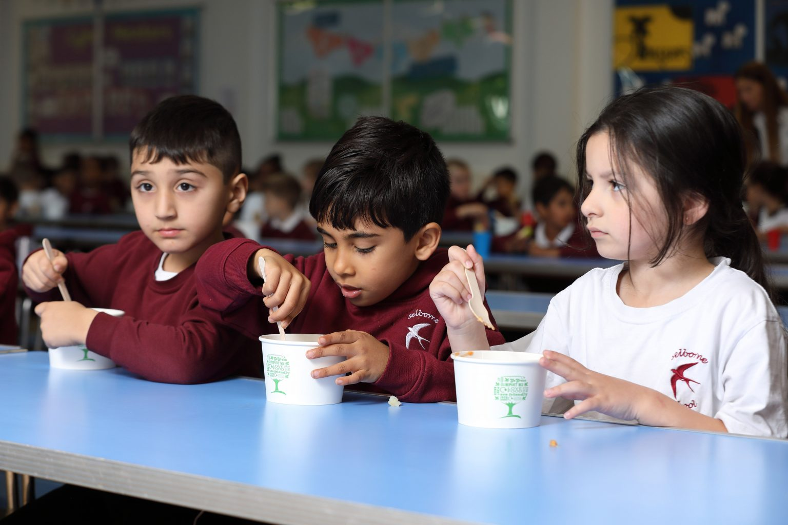 Three children eating food at a table at school