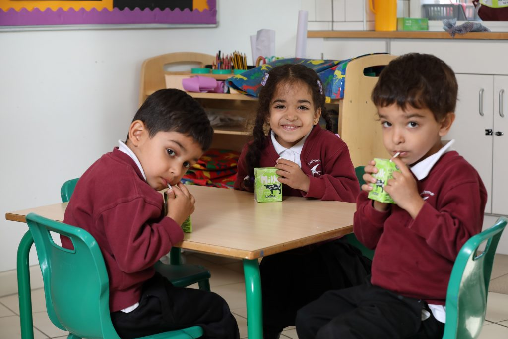 Three children at a desk at school having a drink