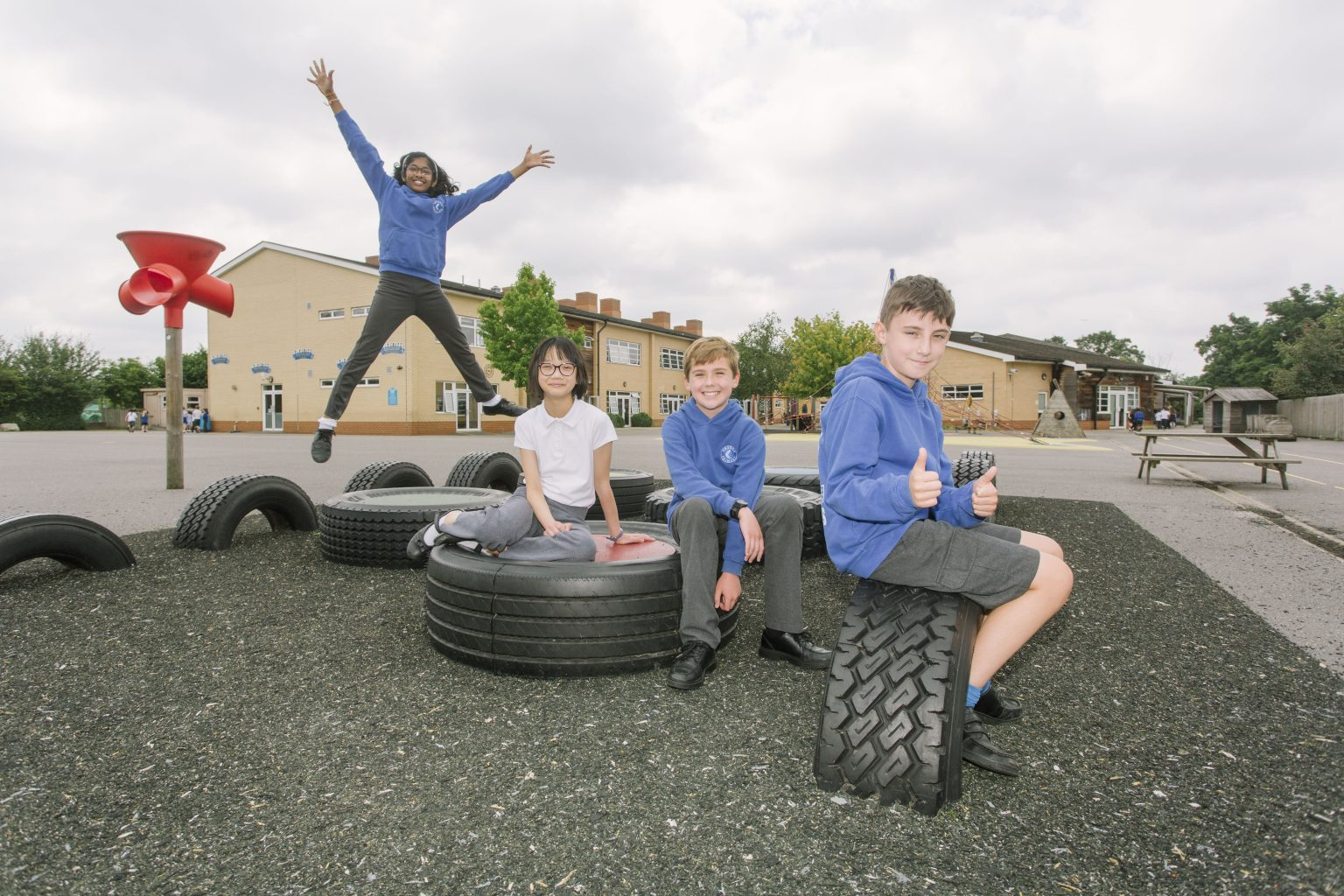 Grange Primary School pupils in the playground - one jumping in the air, one sitting with his thumbs up