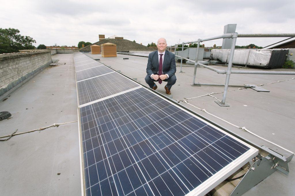 Grange Primary School headteacher Jamie Maloy on the roof next to solar panels