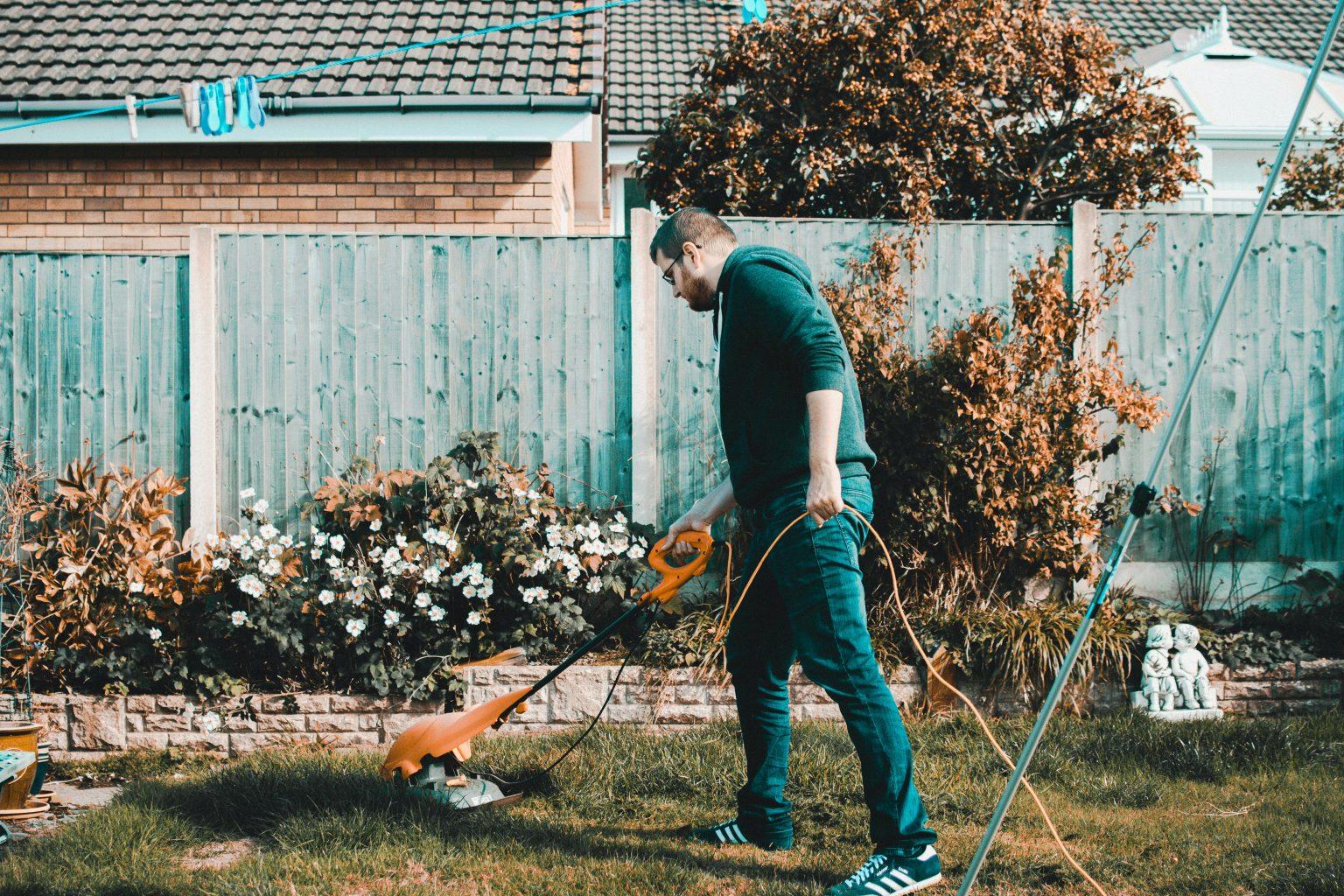 man mowing lawn in garden