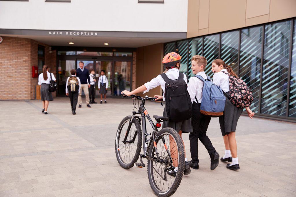 School children walking and wheeling bikes towards the school entrance