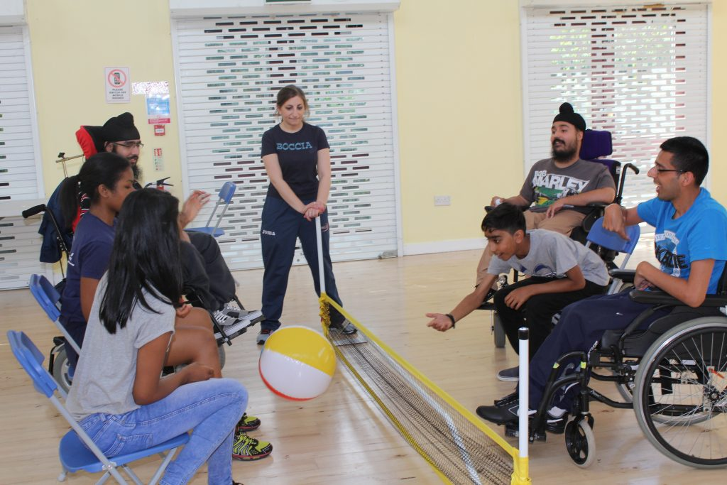 Disabled people in wheelchairs and sitting on chairs, playing volleyball