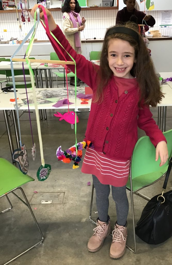 girl holding up mobile that she has created