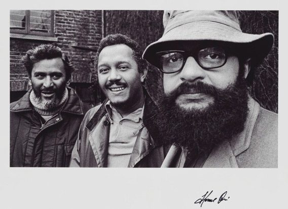 Three men looking at the camera. They are writers Samuel Selvon, John La Rose, and Andrew Salkey. It was taken by photographer Horace Ové